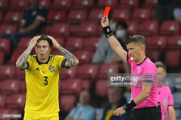 Italian referee Daniele Orsato gives a red card to Sweden's defender Marcus Danielsson for a foul on Ukraine's forward Artem Besedin during the UEFA...