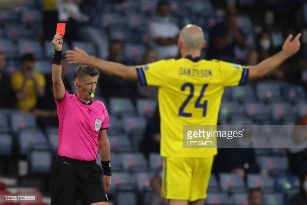 Italian referee Daniele Orsato shows a red card to Sweden's defender Marcus Danielsson during the UEFA EURO 2020 round of 16 football match between...