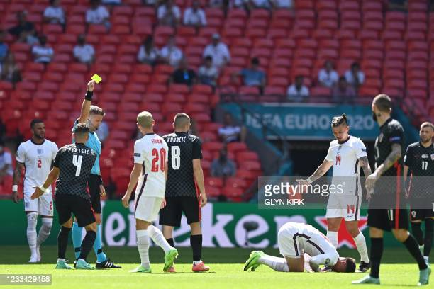 Italian referee Daniele Orsato shows a yellow card to Croatia's midfielder Mateo Kovacic during the UEFA EURO 2020 Group D football match between...