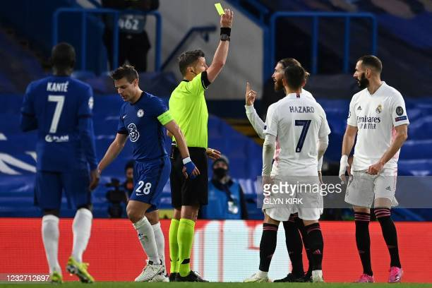 Italian referee Daniele Orsato shows a yellow card to Real Madrid's Spanish defender Sergio Ramos for his foul on Chelsea's Spanish defender Cesar...