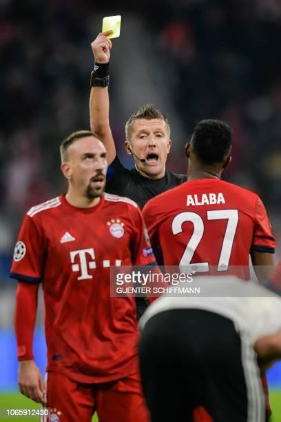 Italian referee Daniele Orsato shows Bayern Munich's Austrian defender David Alaba the yellow card during the UEFA Champions League Group E football...