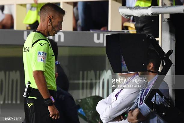 Italian referee Davide Massa checks the VAR assistant referee viedo screen during the Italian Serie A football match Fiorentina vs Napoli on August...