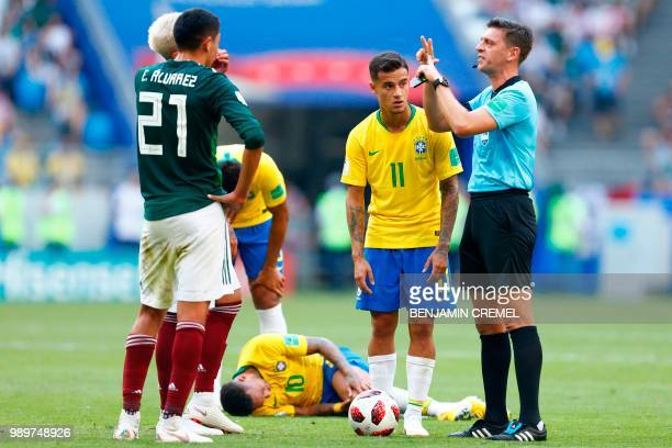 Italian referee Gianluca Rocchi gestures beside Brazil's forward Philippe Coutinho as Brazil's forward Neymar lies on the ground after being fouled...