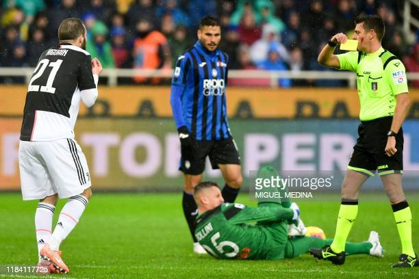 Italian referee Gianluca Rocchi gives a yellow card to Juventus' Argentinian forward Gonzalo Higuain during the Italian Serie A football match...