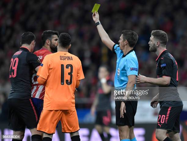 Italian referee Gianluca Rocchi shows a yellow card to Atletico Madrid's Spanish forward Diego Costa during the UEFA Europa League semifinal second...