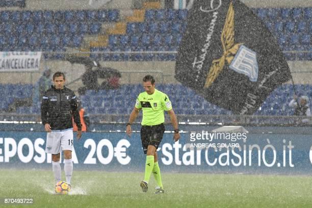Italian referee Luca Banti and Lazio's captain from BosniaHerzegovina Senad Lulic control the pitch under heavy rain before the start of the Italian...