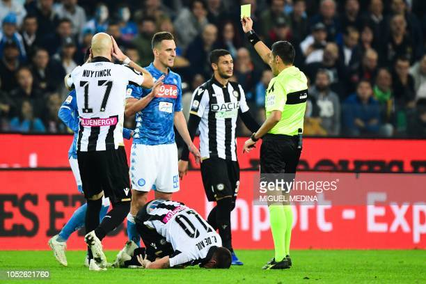 Italian referee Maurizio Mariani gives a yellow card to Napoli's Polish forward Arkadiusz Milik after he tackled Udinese's Argentine midfielder...