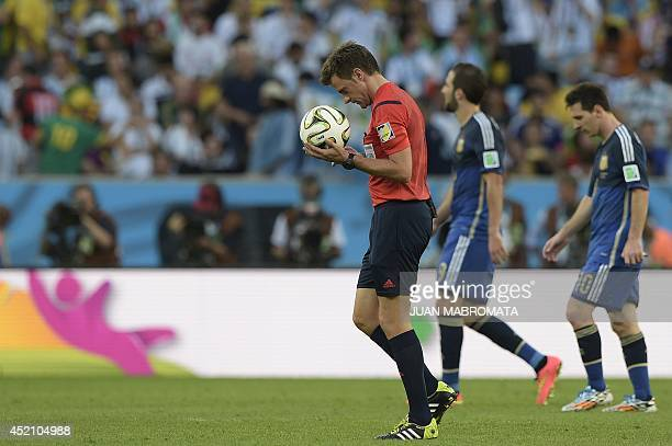 Italian referee Nicola Rizzoli walks with the ball following the first half of the 2014 FIFA World Cup final football match between Germany and...