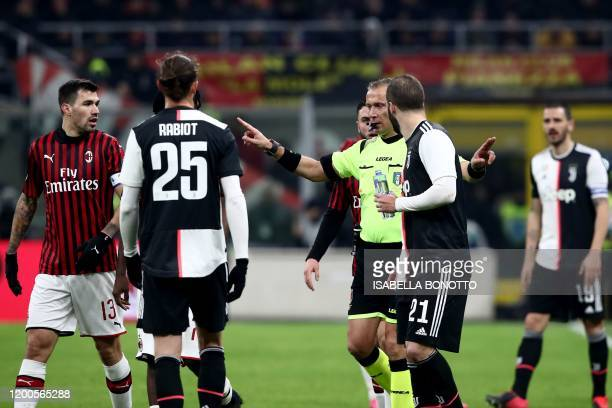 Italian referee Paolo Valeri gestures after granting a penalty to Juventus during the Italian Cup semifinal first leg football match AC Milan vs...