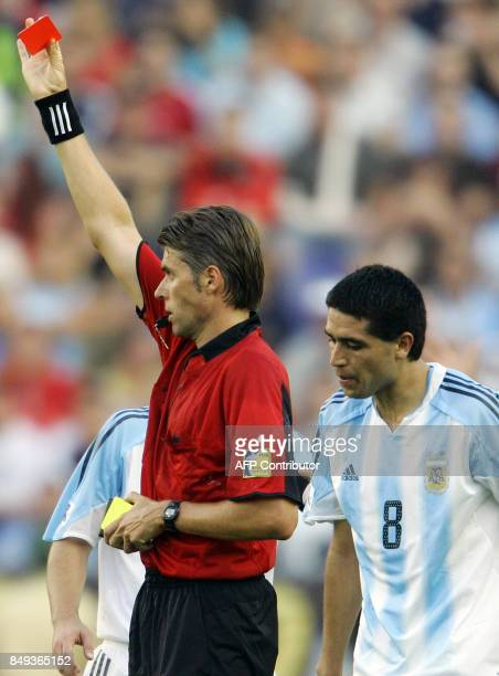 Italian referee Roberto Rosetti delivers a red card to Argentine Javier Saviola as midfielder Juan Riquelme talks to him during the 2005 FIFA...