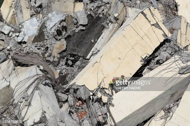 TOPSHOT Italian rescuers climb onto the rubble of the collapsed Morandi motorway bridge to look for victims and survivors in the northern port city...