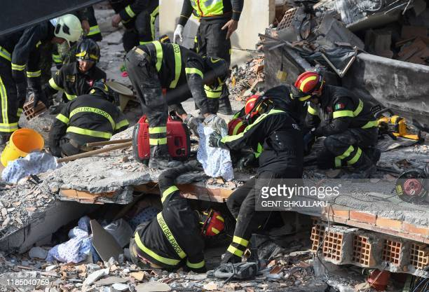 Italian rescuers of the Vigili del Fuoco search for survivors through the rubble of a collapsed building on November 27 in Thumane northwest of the...
