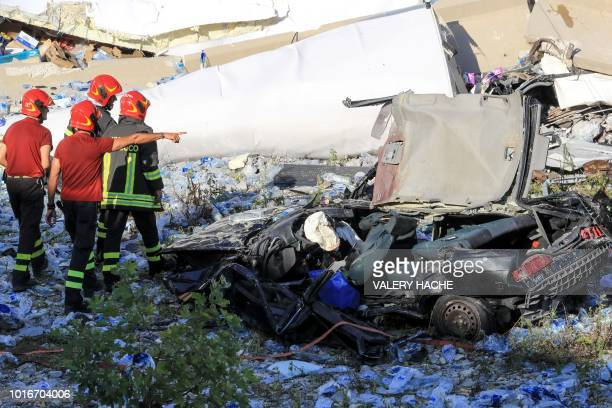 Italian rescuers search the scene of the collapsed Morandi motorway bridge to look for victims and survivors in the northern port city of Genoa on...