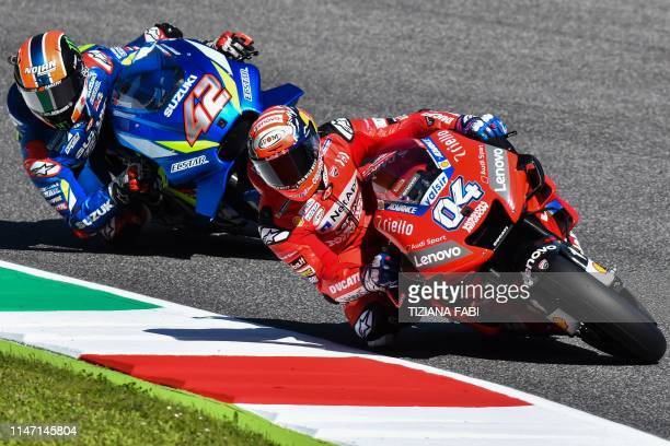 Italian rider Andrea Dovizioso rides his Ducati and Spanish rider Alex Rins rides his Suzuki during a free practice session for the Italian Moto GP...