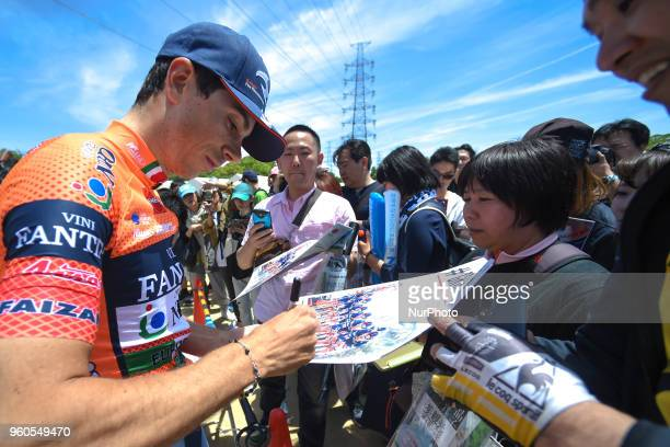 Italian rider Marco Canola from team NippoVini Fantini signs autographs to his fans ahead of the opening stage 26km Individual Time Trial in Daisen...