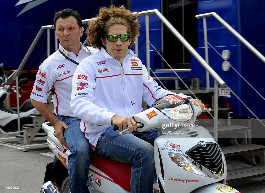 Italian rider Marco Simoncelli (R) and team manager Italian Fausto Gresini (L) arrive at the race control to declare a crash with Dani Pedrosa at the Catalunya Grand Prix at the Montmelo racetrack on June 2, 2011 in Montmelo, near Barcelona.