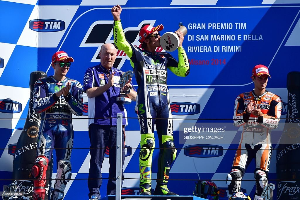 Italian rider (Yamaha) Valentino Rossi (C) celebrates on the podium after winning the MotoGP race ahead of teammate Spanish rider (Yamaha) Jorge Lorenzo (L) and Marc Marquez (R) on September 14, 2014 at the Misano World Circuit Marco Simoncelli in San Marino.