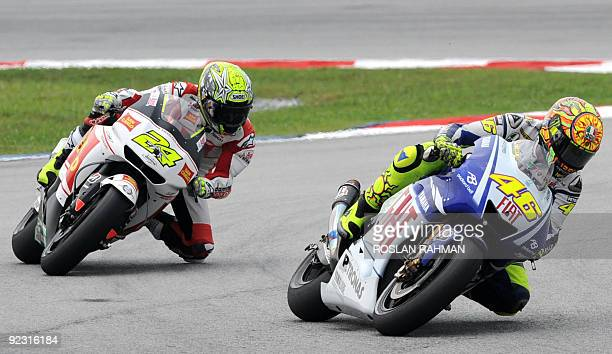 Italian rider Valentino Rossi of Fiat Yamaha and Spanish rider Toni Elias of San Carlo Honda take a corner in the qualifying practice for the...