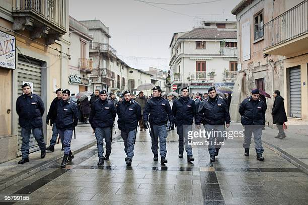 Italian Riots Police secure Rosarno residents during a peaceful protest as they march through the city's flat concrete grid on January 11 2010 in...