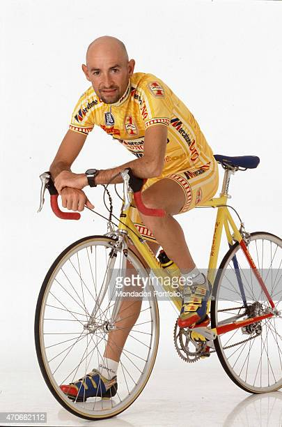 """""""Italian road racing cyclist Marco Pantani poses in a photo studio mounting his bicycle, his arms resting on the handlebars and a foot on the ground;..."""