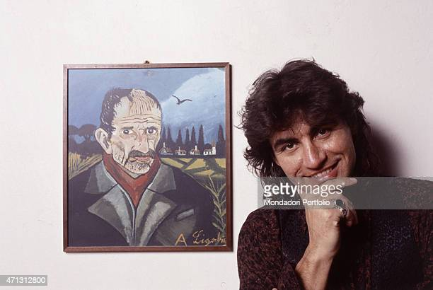 Italian rocker Luciano Ligabue, come adulto to success and on his second album at the time the photo was taken, poses alongside a self-portrait of...