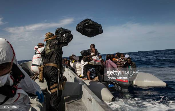Italian sailors with the Uraniam Navy Ship throw lifejackets to 109 African migrants from Gambia Mali Senegal Ivory Coast Guinea and Nigeria as the...