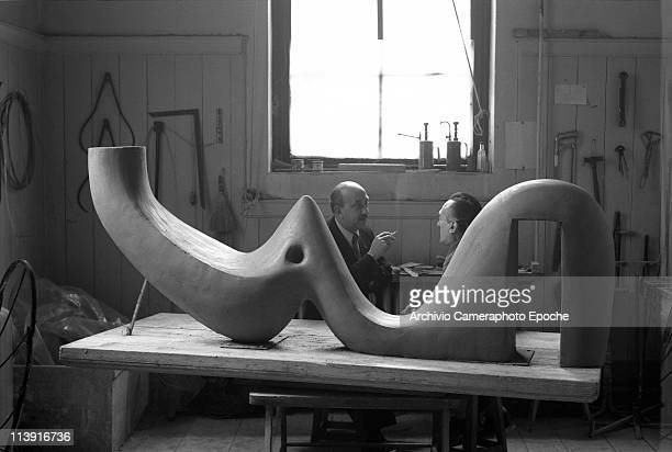 Italian sculptor Alberto Viani chatting with a smoking man in Viani's studio behind a rough sculpture Many tools stuck on the walls Venice 1966