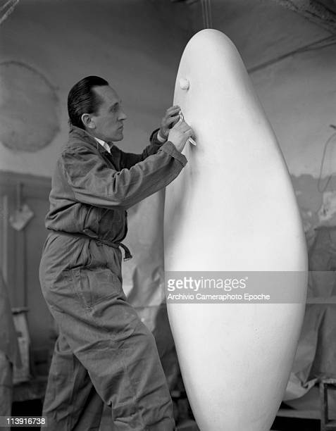 Italian sculptor Alberto Viani standing in front of one of his sculptures refining details and wearing an overalls in his sudio Venice 1952
