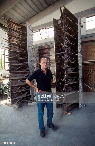 Italian sculptor Arnaldo Pomodoro inside his study in Milan poses in front of the sculpture he has made for the new Mondadori headquarters in Segrate...