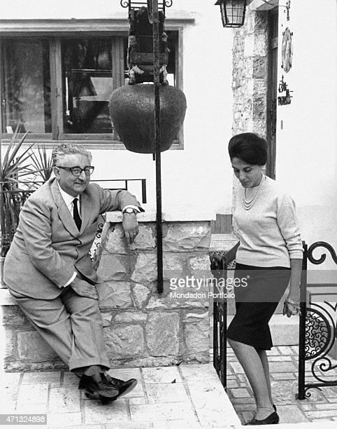 Italian senator and future President of the Italian Republic Giovanni Leone sitting under a big cowbell beside his wife Vittoria Michitto ....