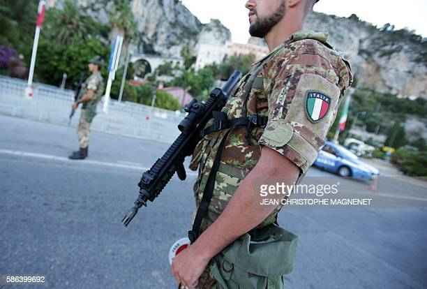 Italian servicemen stand guard and check vehicles at the SaintLudovic gate at the ItalianFrench border on August 6 in Ventimiglia Italy A group of...