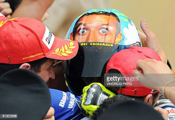 Italian seventime former world champion Valentino Rossi riding a Yamaha is congratulated by team members after winning his home Moto Grand Prix at...