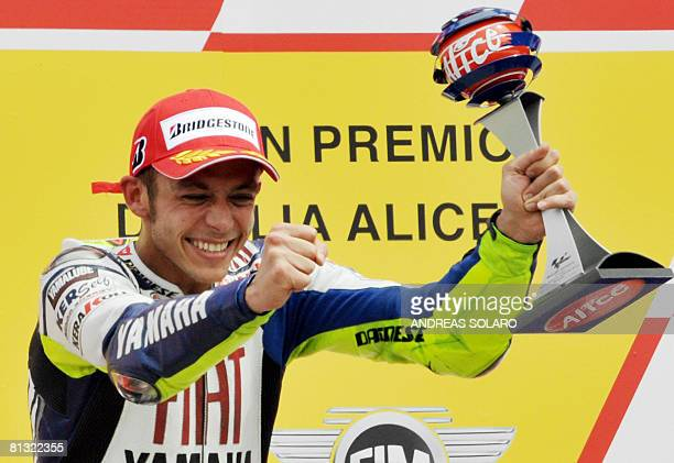 Italian seven-time former world champion Valentino Rossi, riding a Yamaha, holds the trophy on th podium after winning his home Moto Grand Prix at...