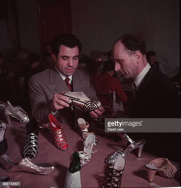 Italian shoe designer Salvatore Ferragamo discussing a selection of his shoes
