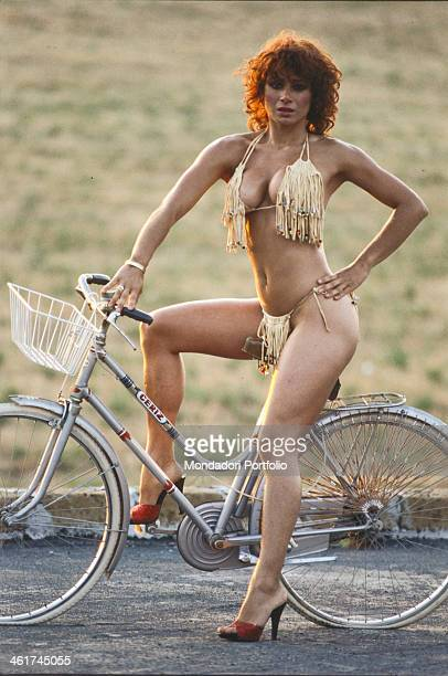 Italian showgirl Carmen Russo posing sitting on a bicycle wearing a bikini 1980