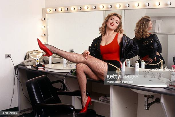 Italian showgirl Paola Barale sitting on the counter of his dressing room lifts her legs in the air in a seductive pose on 1992 in Italy