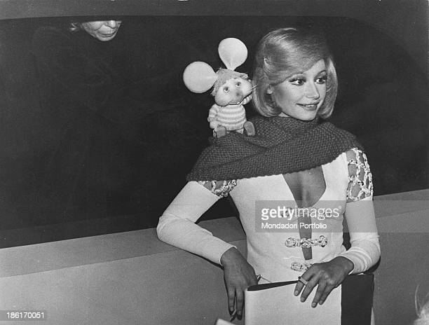 Italian showgirl Raffaella Carrà smiling with Topo Gigio on her shoulder during the rehearsals of the TV variety show Canzonissima Rome 1974