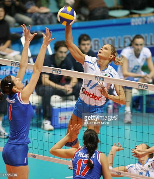 Italian Simona Gioli hits the ball over Serbian blockers Jelena Nikolic and Stefana Veljkovic during their second round match at the women's World...