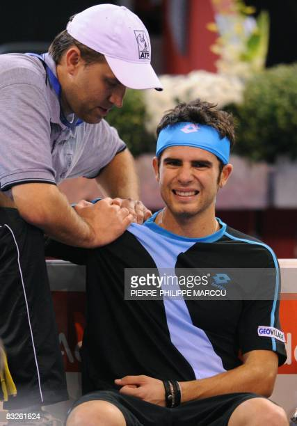 Italian Simone Bolelli is treated after injuring his shoulder during a second round tennis match against Britain's Andy Murray at the Masters in...