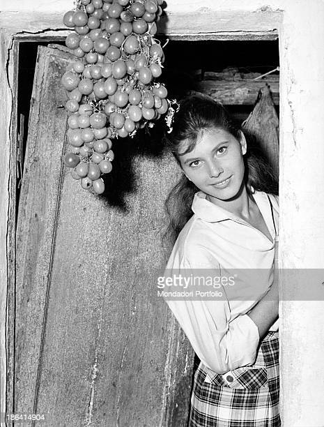 Italian singer actress and record producer Claudia Mori smiling leaning against a door Italy 1959