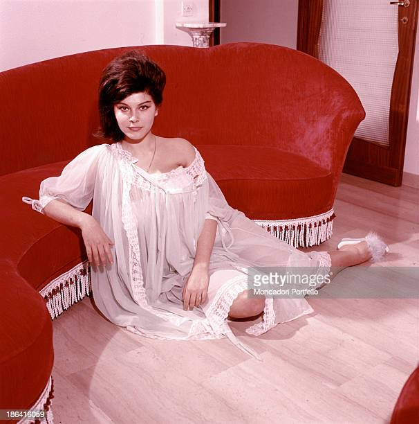 Italian singer actress and record producer Claudia Mori wearing a nightdress sitting at the foot of a red sofa Italy 1960s