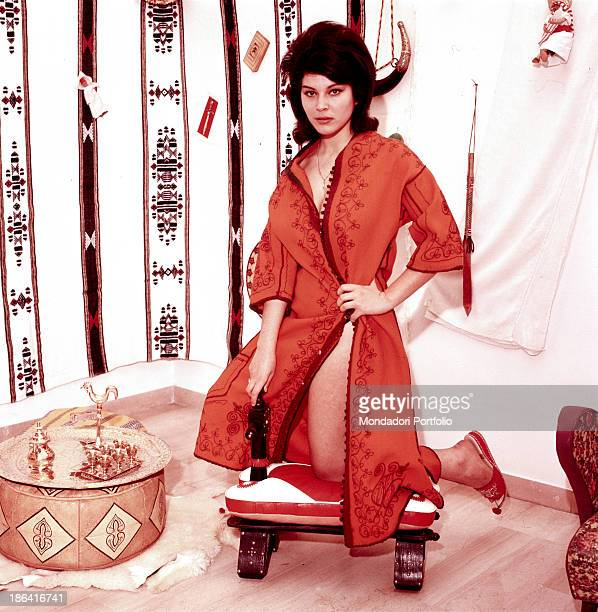 Italian singer actress and record producer Claudia Mori wearing an oriental dress kneeling on a stuffed stool Italy 1960s