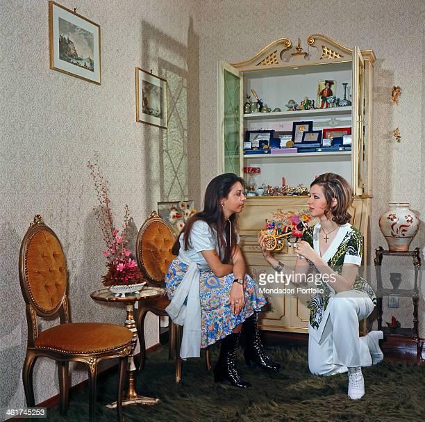 Italian singer actress TV presenter Loretta Goggi showing a Sicilian cart to her little sister and Italian singer actress TV presenter Daniela Goggi...