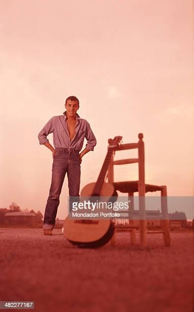 Italian singer Adriano Celentano posing beside his guitar at the 11th Sanremo Music Festival Sanremo 1961