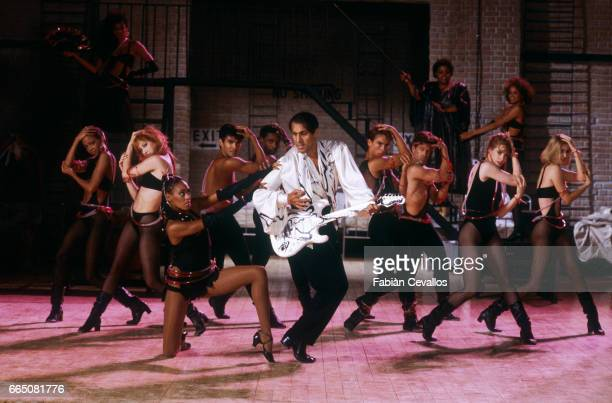 Italian singer Adriano Celentano who interprets the title role and directs the film Joan Lui appears on stage during a dance number with other cast...