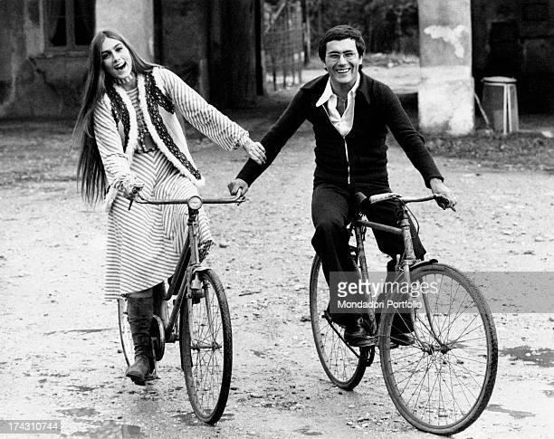 Italian singer Al Bano and his wife Americanborn Italian singer Romina Power posing smiling on their bicycles Milan 1970s