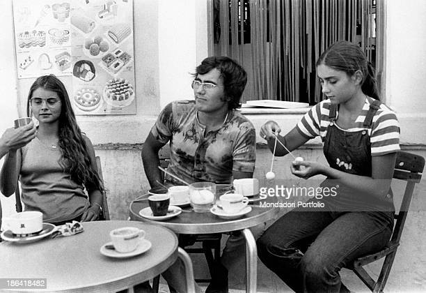 Italian singer Al Bano born Albano Carrisi seated at the table of a bar has breakfast together with his wife Romina Power and her younger sister...