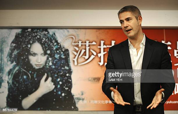 Italian singer Alessandro Safina gestures in front of a poster of British singer Sarah Brightman during a press conference in Taipei on April 3 2009...