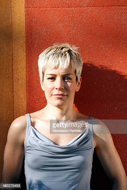 Italian singer Alexia, born Alessia Aquilani, posing in a half-length portrait on the background of a red wall during a holiday in Liguria. Santa...