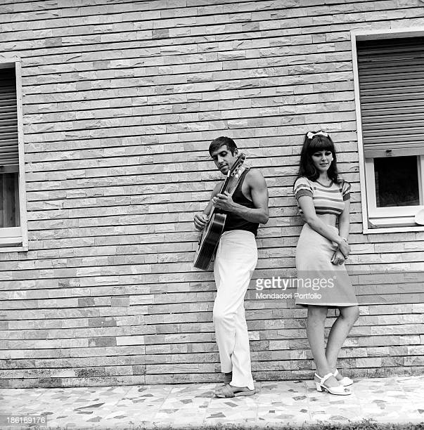 Italian singer and actor Adriano Celentano and his wife Italian actress Claudia Mori posing leaning against the wall of a house Le Focette August 1967
